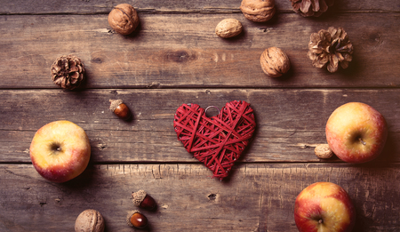 cone shaped: photo of the delicious apples, fir-cones, nuts, and red heart shaped toy on the brown wooden background