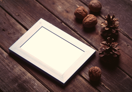 fall harvest: photo of the white photo frame, nuts and fir-cones on the brown wooden background
