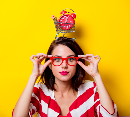 red cardigan: portrait of the beautiful young woman with cart for shopping and red alarm clock on the head on the yellow background
