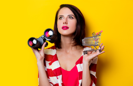 red cardigan: portrait of the beautiful young woman with cart for shopping and binoculars on the yellow background Stock Photo