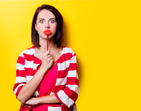 wondered: portrait of the beautiful young woman with lip shaped toy on the yellow background