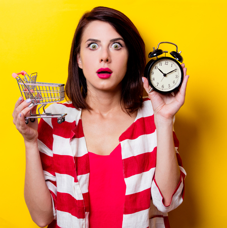 wondered: portrait of the beautiful young woman with cart for shopping and black alarm clock on the yellow background