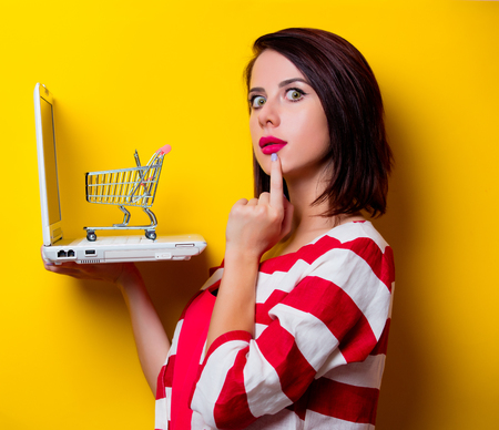 wondered: photo of the beautiful young woman with cart and laptop on the yellow background
