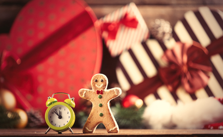 photo of the alarm clock and gingerbread man on the christmas decorations background Stock Photo