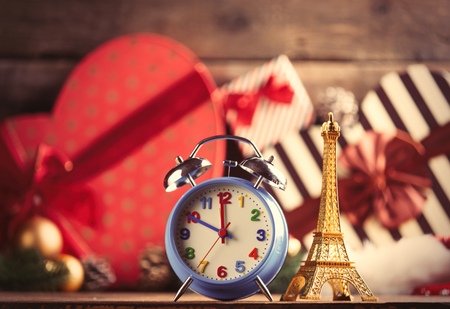 photo of the eiffel tower shaped toy and alarm clock on the christmas decorations background