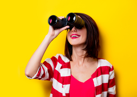 look pleased: portrait of the beautiful yound woman with binoculars on the yellow background