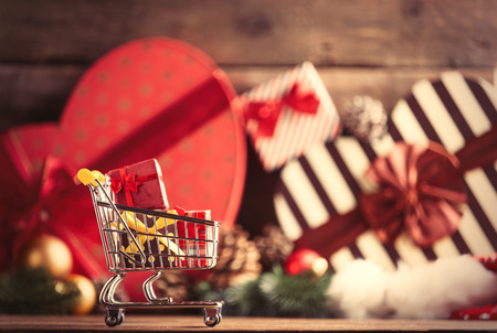 photo of the cart for shopping with gifts on the christmas decorations background Stock Photo