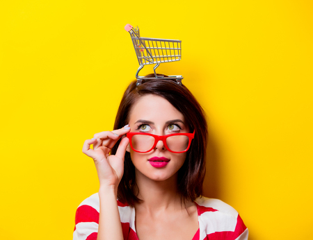 red cardigan: portrait of the beautiful young woman with cart for shopping on the yellow background