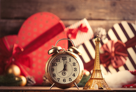 boxing day: photo of the eiffel tower shaped toy and alarm clock on the christmas decorations background