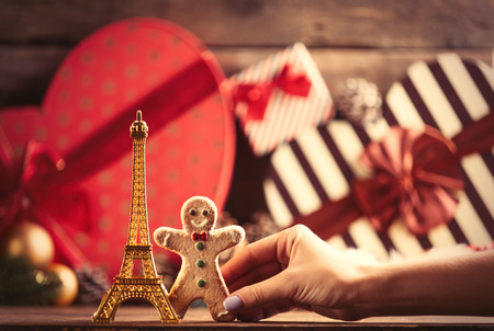 photo of the eiffel tower shaped toy and gingerbread man on the christmas decorations background