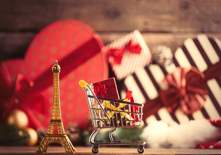 photo of the eiffel tower shaped toy and cart for shopping on the christmas decorations background Stock Photo