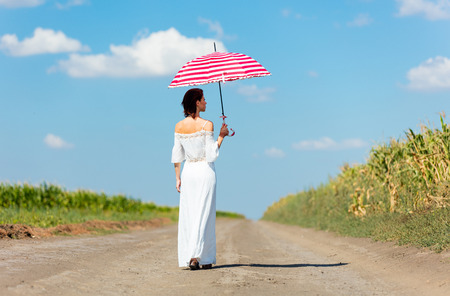 umbrela: photo of the beautiful young woman with umbrella walking on the road