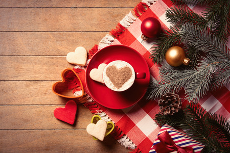 photo of the cup of coffee, cookies and christmas decorations on the brown wooden background