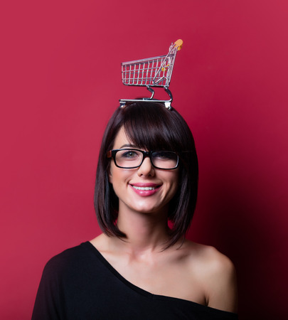 vinous: portrait of the beautiful young woman with shopping cart on her head on the vinous background