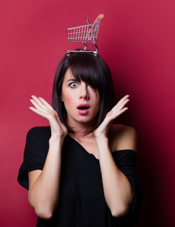 portrait of the beautiful surprised young woman with shopping cart on her head on the vinous background