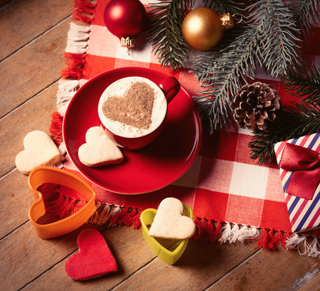 boxing day: photo of the cup of coffee, cookies and christmas decorations on the brown wooden background