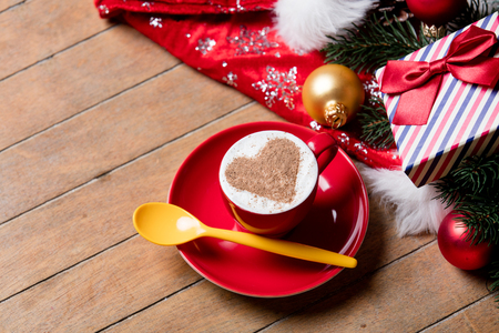 photo of the cup of coffee and christmas decorations on the brown wooden background Stock Photo
