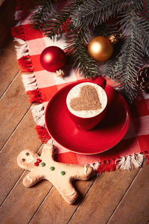 photo of the cup of coffee gingerbread man and christmas decorations on the brown wooden