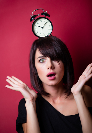 portrait of the beautiful young woman with alarm clock on her head on the vinous background
