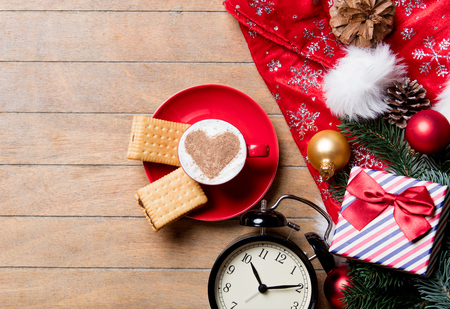 photo of the cup of coffee, alarm clock, cookies and christmas decorations on the brown wooden background Stock Photo