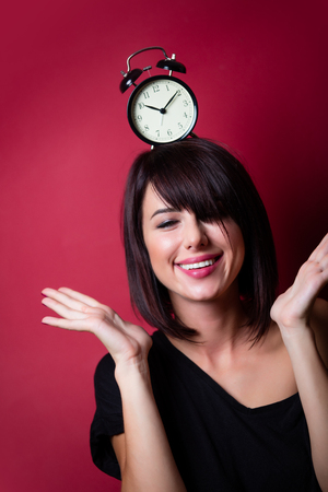 vinous: portrait of the beautiful young woman with alarm clock on her head on the vinous background