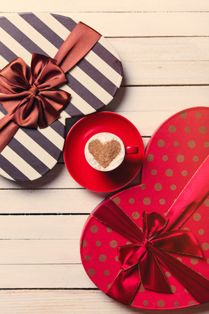 photo of the cup of coffee and heart shaped gifts on the white wooden background Stock Photo
