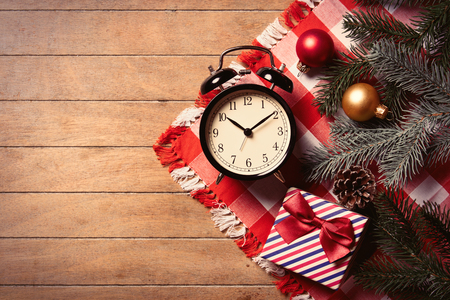 photo of the alarm clock and christmas decorations on the brown wooden background