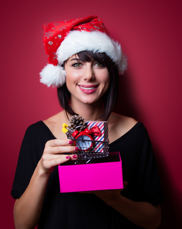 vinous: portrait of the beautiful young woman with shopping cart and gifts on the vinous background Stock Photo