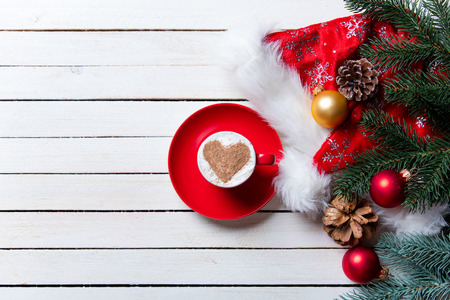 photo of the cup of coffee and christmas decorations on the white wooden background Stock Photo