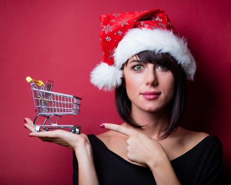 vinous: portrait of the beautiful young woman with shopping cart on the vinous background Stock Photo