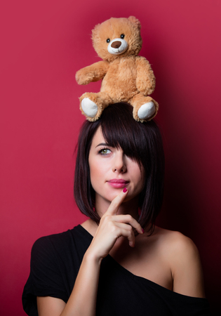 vinous: portrait of the beautiful young woman with teddy bear on the vinous background