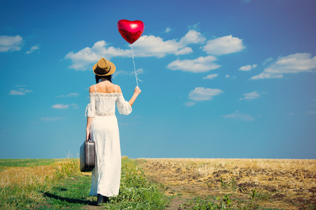 people travelling: photo of the beautiful young woman with heart-shaped balloon and suitcase in the field