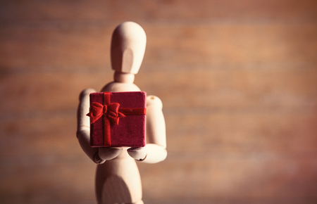 poppet: photo of the beautiful gestalta with gift on the brown wooden background