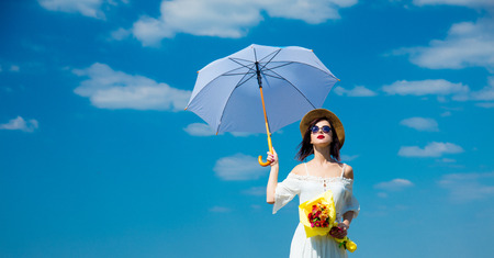 photo of the beautiful young woman with bouquet and umbrella on the sky background Stock Photo