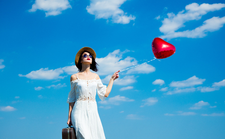 people travelling: photo of the beautiful young woman with heart-shaped balloon and suitcase on the sky background
