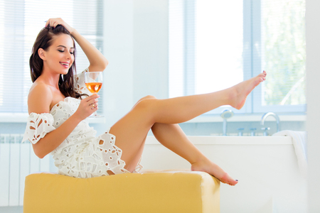photo of the beautiful young woman  sitting on the ottoman with a drink Stock Photo
