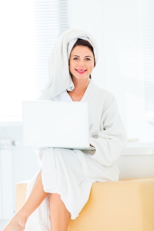 portrait of the beautiful young woman sitting on the ottoman and holding a laptop