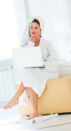 photo of the beautiful young woman sitting on the ottoman and holding a laptop
