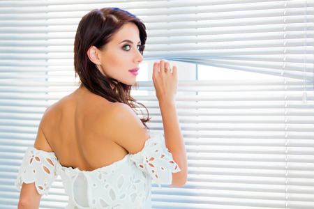 jalousie: photo of the beautiful young woman standing near the window and looking through the jalousie