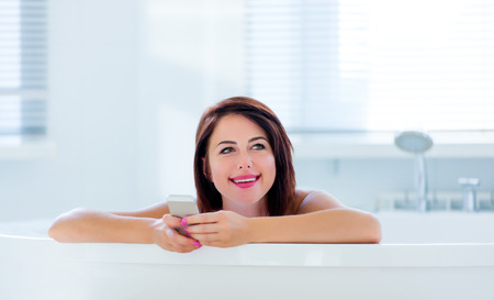 photo of the beautiful young woman having a bath and using her mobile phone