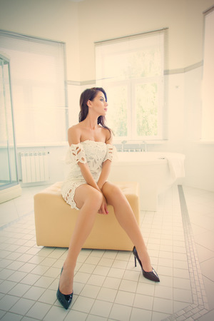 photo of the beautiful young woman sitting on the ottoman near the bath