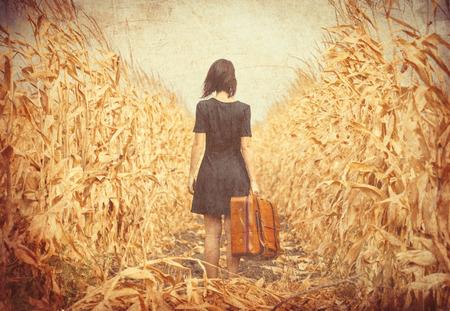 photo de la belle jeune femme avec une valise debout au milieu du champ