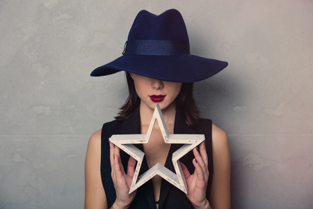 Portrait of a style brunette woman in hat with star shape on grey background Stock Photo