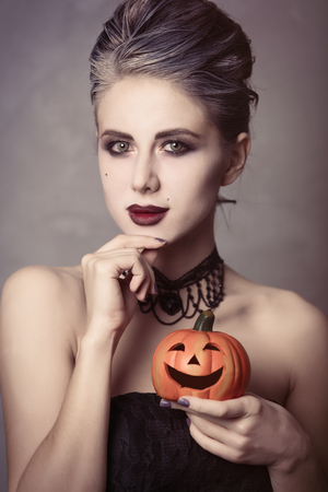 Portrait of young woman in witch halloween costume with pumpkin, smiling over grey background