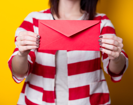 Young smiling brown hair adult girl holding red gift envelope on yellow background