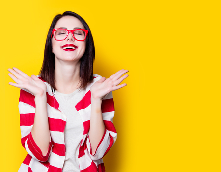 puntualidad: Portrait of a yung style woman in glasses on yellow background Foto de archivo