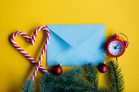 lolipop: Blue christmas envelope and lolipop with alarm clock on yellow background