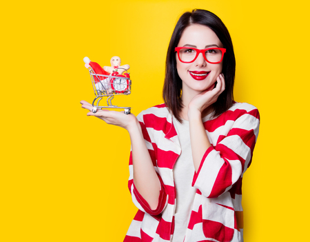 Portrait of a young woman in glasses with shopping cart full of christmas gifts on yellow background Stock Photo