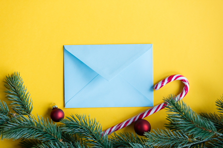 Blue christmas envelope and lolipop on yellow background Stock Photo
