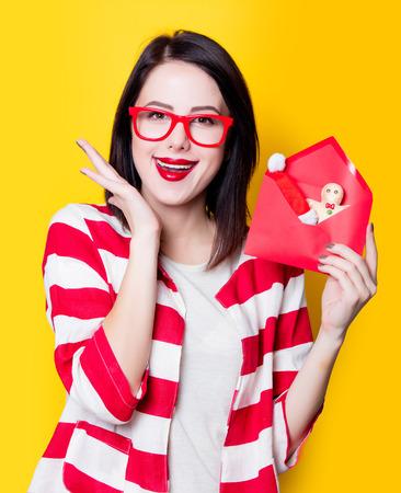 puntualidad: Mujer joven con el sobre lleno de regalos de Navidad sobre fondo amarillo